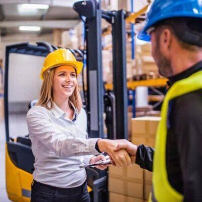 Chica trabajadora dándole la mano a su jefe.