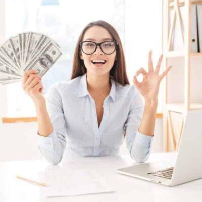 Chica sonriendo con dinero en la mano.